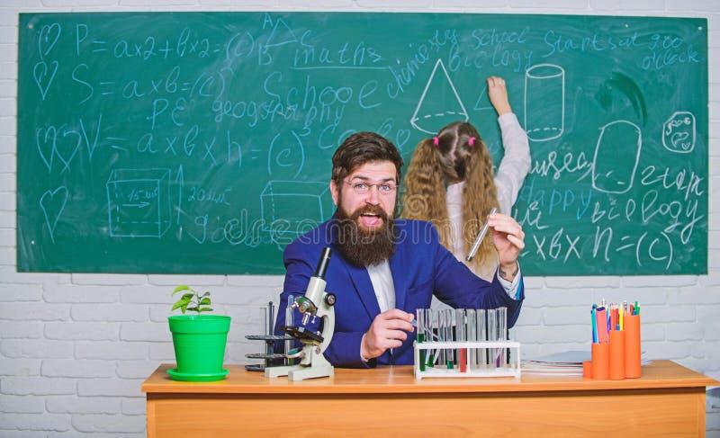 F?rklaring av biologi till barn Sk?ggigt l?rarearbete f?r man med mikroskopet och provr?r i biologiklassrum _ arkivfoto