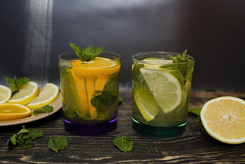 F?rnyande lemonad f?r sommar med mintkaramellen och den orange drinken med mintkaramellen m?rkt tr? f?r bakgrund Slapp fokus royaltyfria foton