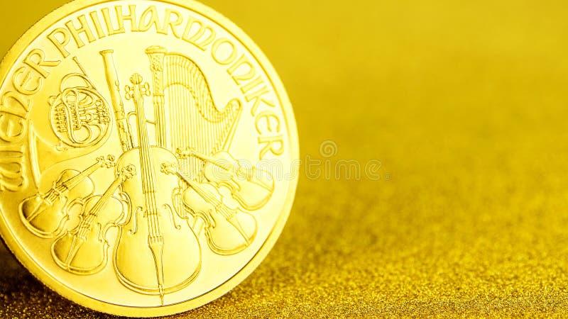 F?rsilvra och guld- ?sterrikiska phillharmonikers ett uns mynt p? guld- bakgrund arkivfoton