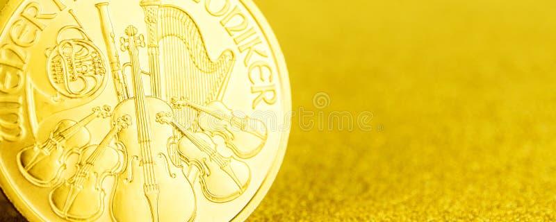 F?rsilvra och guld- ?sterrikiska phillharmonikers ett uns mynt p? guld- bakgrund fotografering för bildbyråer