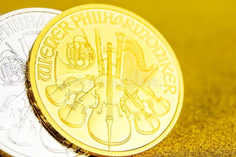 F?rsilvra och guld- ?sterrikiska phillharmonikers ett uns mynt p? guld- bakgrund arkivbilder