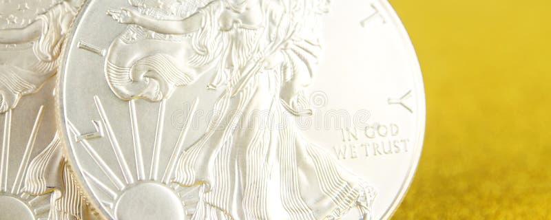 F?rsilvra ?rnen och den guld- amerikanska ?rnen ett uns mynt p? guld- bakgrund royaltyfria bilder