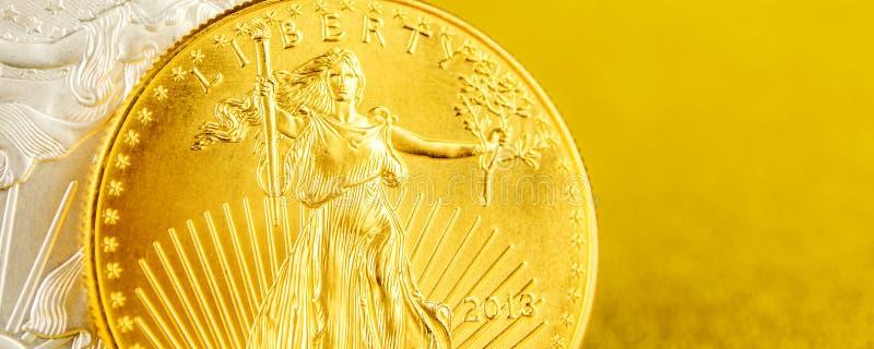 F?rsilvra ?rnen och den guld- amerikanska ?rnen ett uns mynt p? guld- bakgrund fotografering för bildbyråer