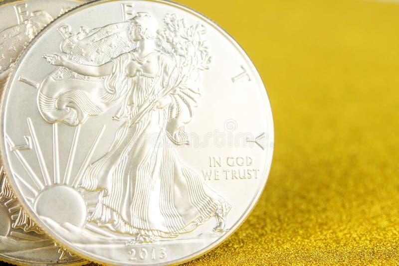 F?rsilvra ?rnen och den guld- amerikanska ?rnen ett uns mynt p? guld- bakgrund arkivfoton