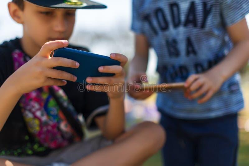 F?rskole- pojkar som spelar p? smartphonen arkivbild