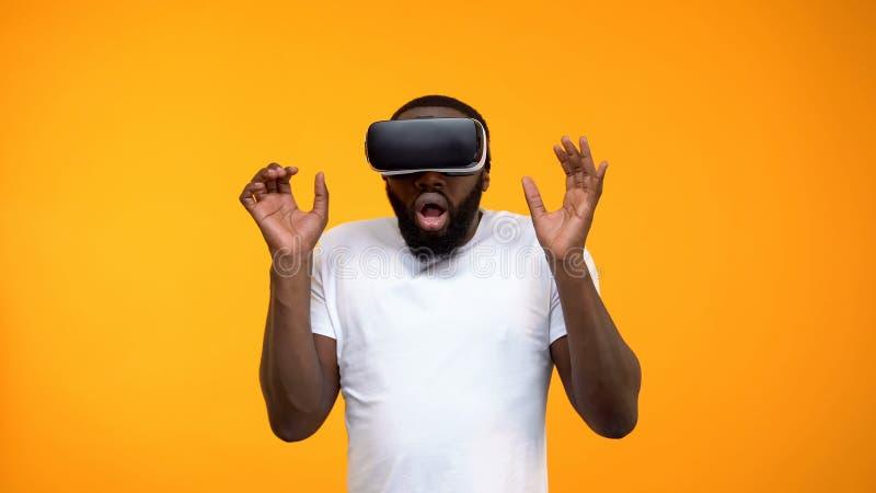 F?rskr?ckt afrikansk amerikanman som anv?nder virtuell verkligheth?rlurar med mikrofon, simulering, n?rbild arkivfoton