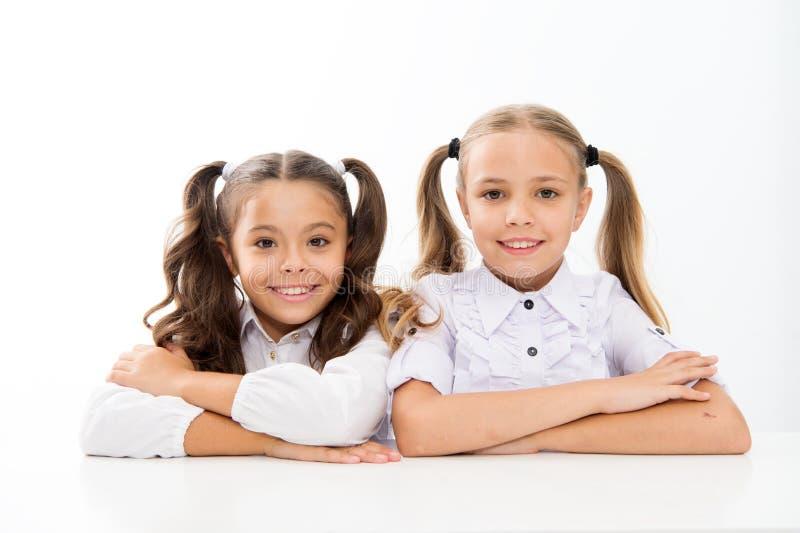F?rsta kvalitet Skolflickor sitter vit bakgrund för skrivbordet Emotionella vänner för skolflickor lycklig barndom Förtjusande sk arkivbild