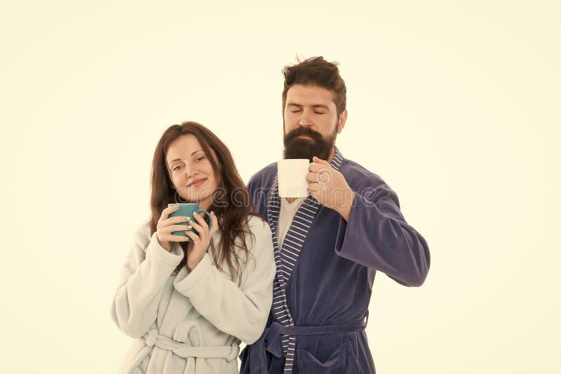 F?rsta smutt i morgon Par kopplar av i morgon med kaffe Familjtraditionsbegrepp Lyckliga par tycker om lat morgon och arkivbild