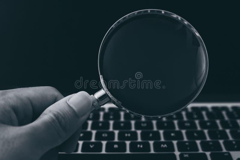 F?rstoringsglas med b?rbar datorbakgrund fotografering för bildbyråer