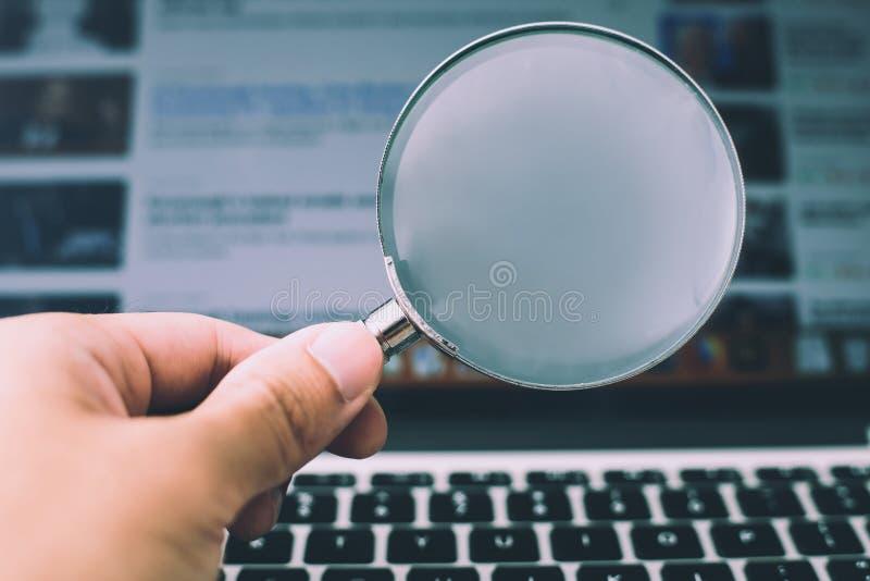 F?rstoringsglas med b?rbar datorbakgrund arkivfoton