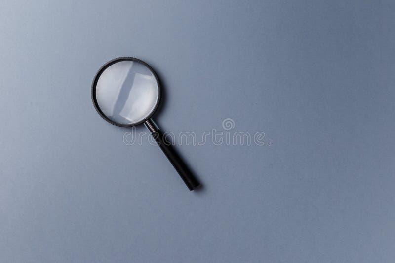F?rstoringsglas p? gr? bakgrund arkivfoton