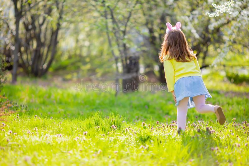 F?rtjusande liten flicka som sitter p? det gr?na gr?set som spelar i tr?dg?rden p? jakt f?r p?sk?gg arkivbilder