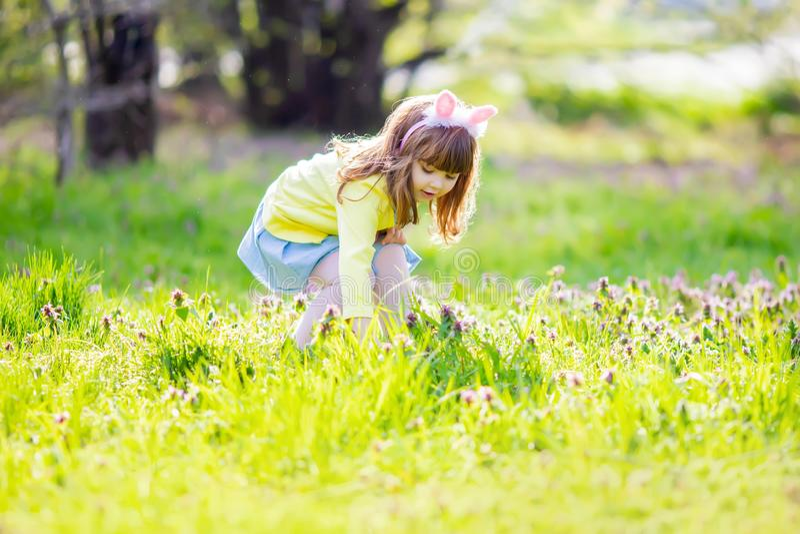 F?rtjusande liten flicka som sitter p? det gr?na gr?set som spelar i tr?dg?rden p? jakt f?r p?sk?gg royaltyfria foton