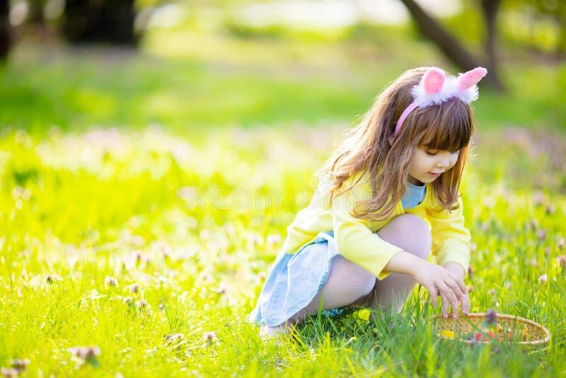 F?rtjusande liten flicka som sitter p? det gr?na gr?set som spelar i tr?dg?rden p? jakt f?r p?sk?gg arkivbild