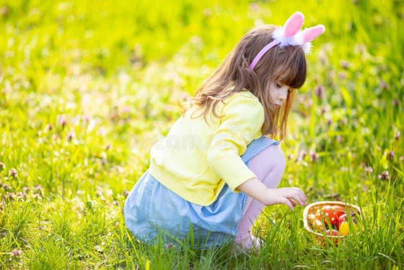 F?rtjusande liten flicka som sitter p? det gr?na gr?set som spelar i tr?dg?rden p? jakt f?r p?sk?gg royaltyfri foto