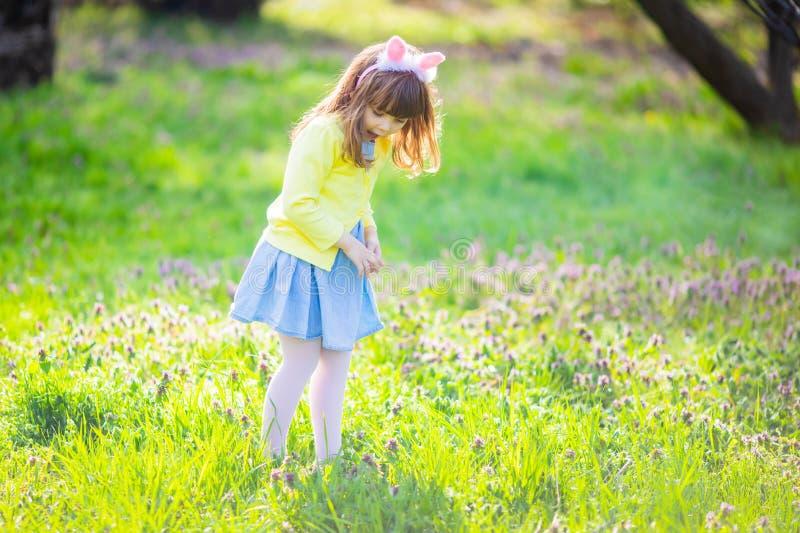 F?rtjusande liten flicka som sitter p? det gr?na gr?set som spelar i tr?dg?rden p? jakt f?r p?sk?gg arkivfoton