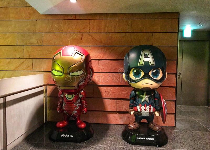 F?RUNDRA SIG ?LDERN AV HJ?LTEutst?llningen som rymmer i Roppongiet Hills Modellen för kapten America och den Iron Man modellen vi royaltyfri foto