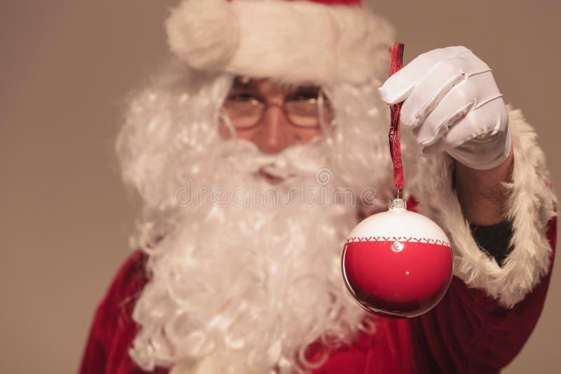 F Santa Claus que presenta una bola de la Navidad a la cámara fotos de archivo