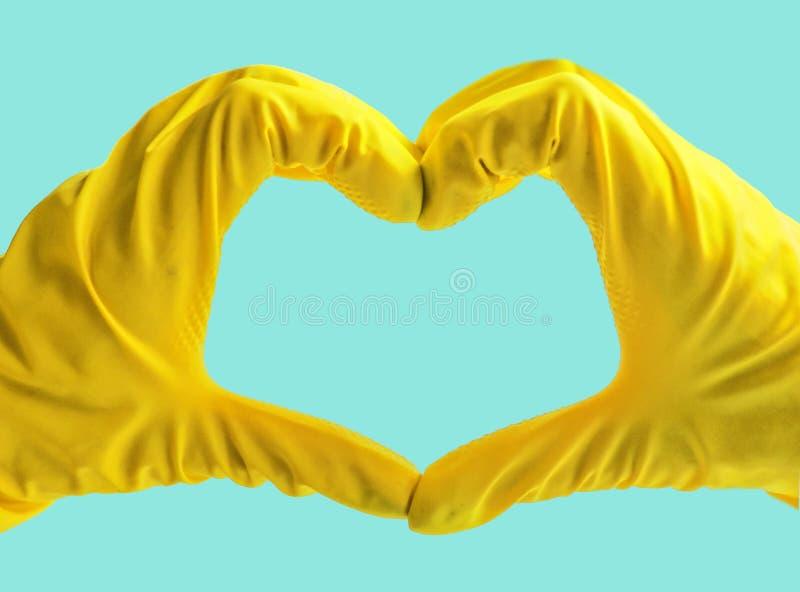 F? startat reng?ra Gula gummihandskar f?r att g?ra ren p? bl? bakgrund Allm?n eller vanlig reng?ring royaltyfri fotografi