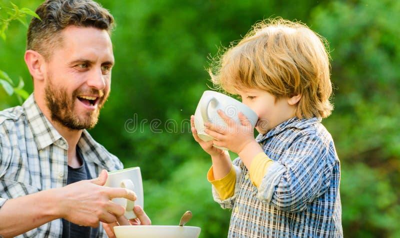 F?tterungssohn nat?rliche Nahrungsmittel Stadium der Entwicklung Gesunde Nahrung Vati und Junge drau?en essen und sich einziehen  stockbild