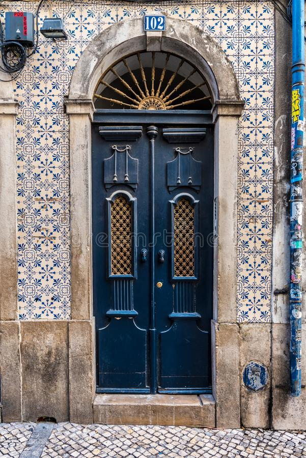 Façade com uma porta de madeira azul e as telhas do azulejo no centro de Lisboa, Portugal fotografia de stock royalty free
