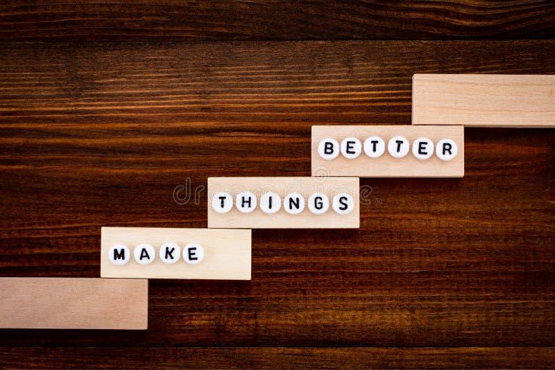 Faça coisas melhorar - o conceito da melhoria, fundo de madeira foto de stock royalty free