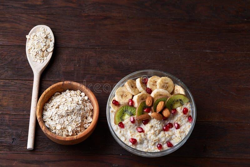 Faça dieta a farinha de aveia do café da manhã com frutos, bacia e colher com flocos da aveia, foco seletivo, close-up fotos de stock royalty free