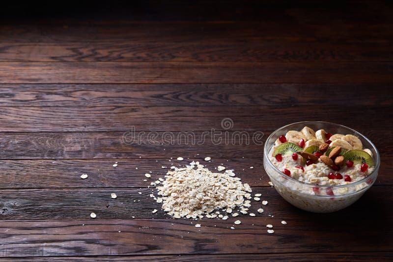 Faça dieta a farinha de aveia do café da manhã com frutos, bacia e colher com flocos da aveia, foco seletivo, close-up fotografia de stock