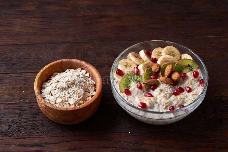 Faça dieta a farinha de aveia do café da manhã com frutos, bacia e colher com flocos da aveia, foco seletivo, close-up fotografia de stock royalty free