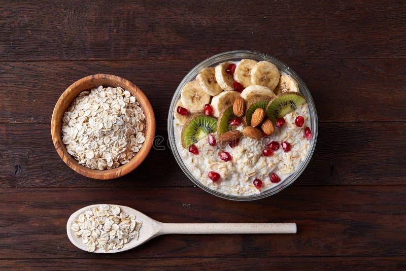 Faça dieta a farinha de aveia do café da manhã com frutos, bacia e colher com flocos da aveia, foco seletivo, close-up foto de stock