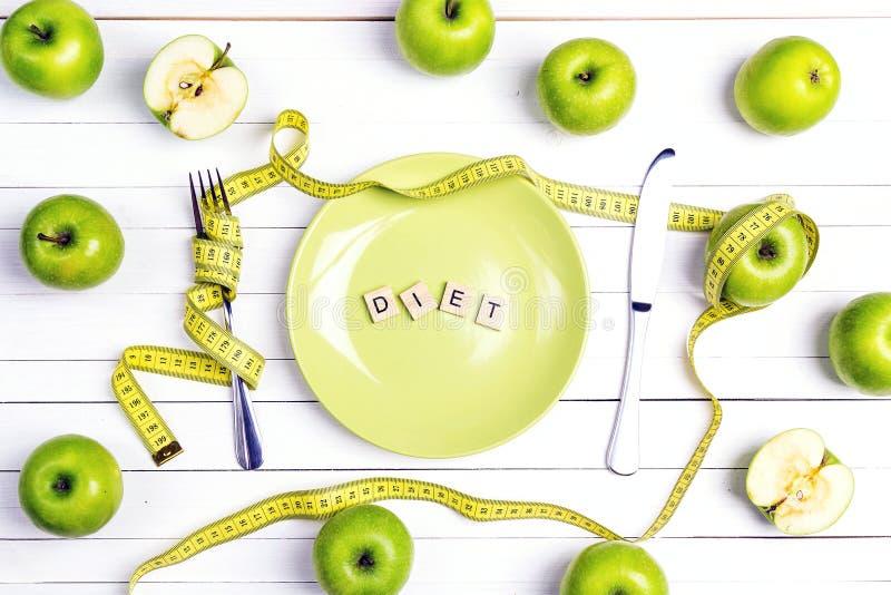 Faça dieta o ajuste da tabela do conceito com cutelaria, fita de medição amarela a fotografia de stock