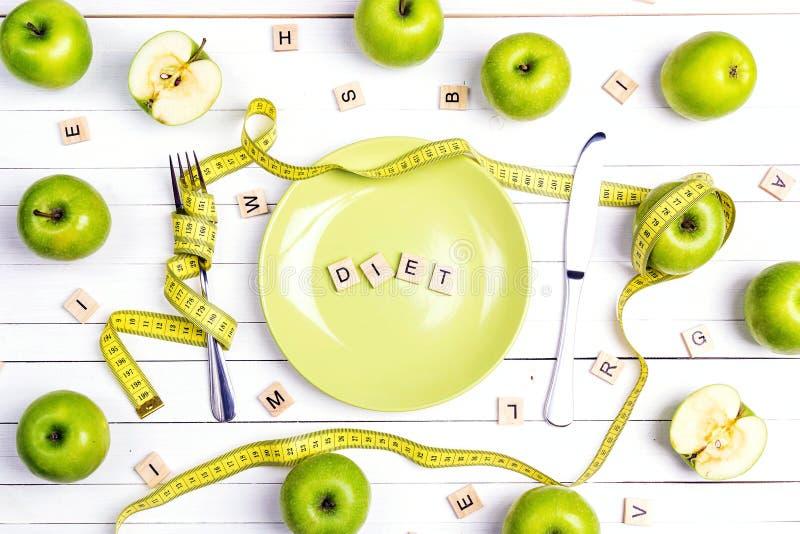 Faça dieta o ajuste da tabela do conceito com cutelaria, a fita de medição amarela e as maçãs verdes na tabela de madeira branca fotografia de stock