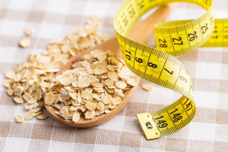 Faça dieta o conceito Farinha de aveia e fita de medição fotografia de stock