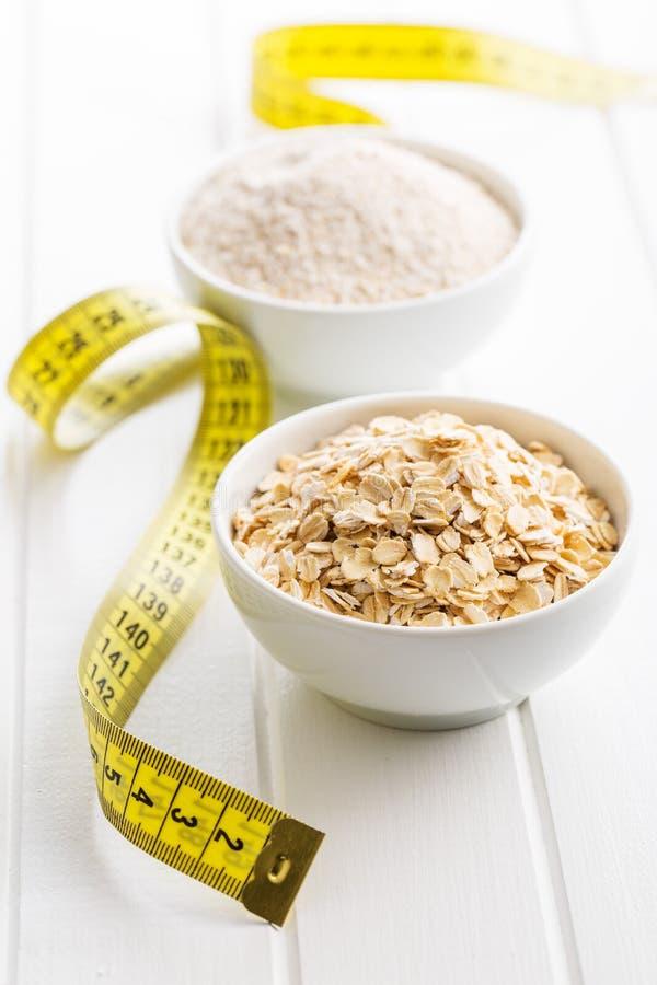 Faça dieta o conceito Farinha de aveia e fita de medição foto de stock