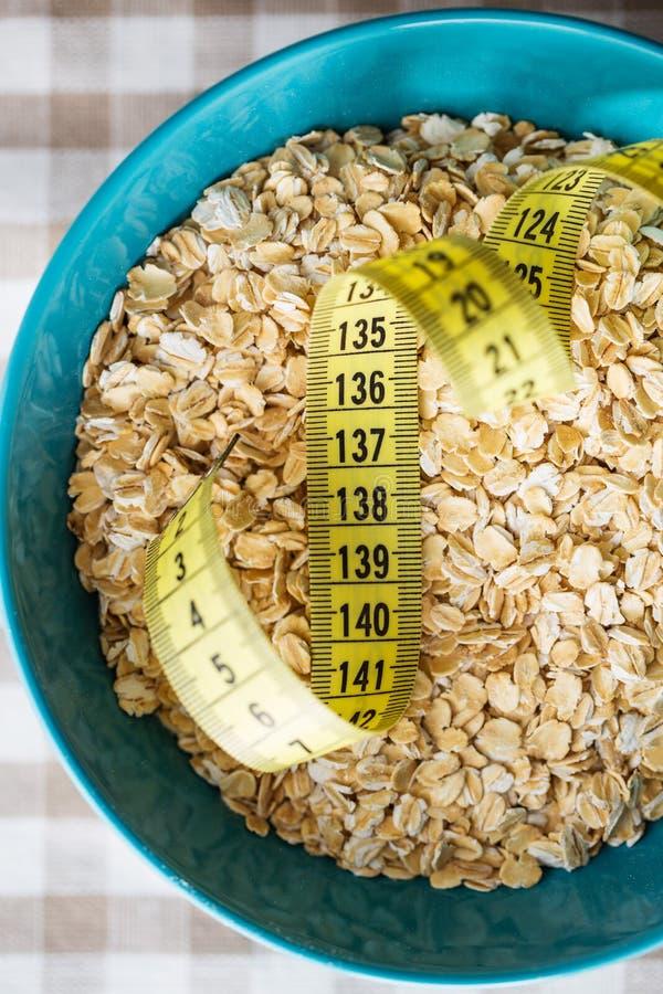Faça dieta o conceito Farinha de aveia e fita de medição fotos de stock royalty free