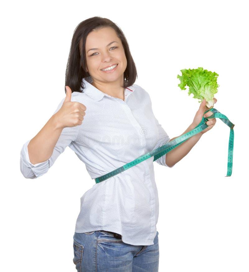 Faça dieta o conceito Jovem mulher com a alface que mede sua cintura w imagem de stock