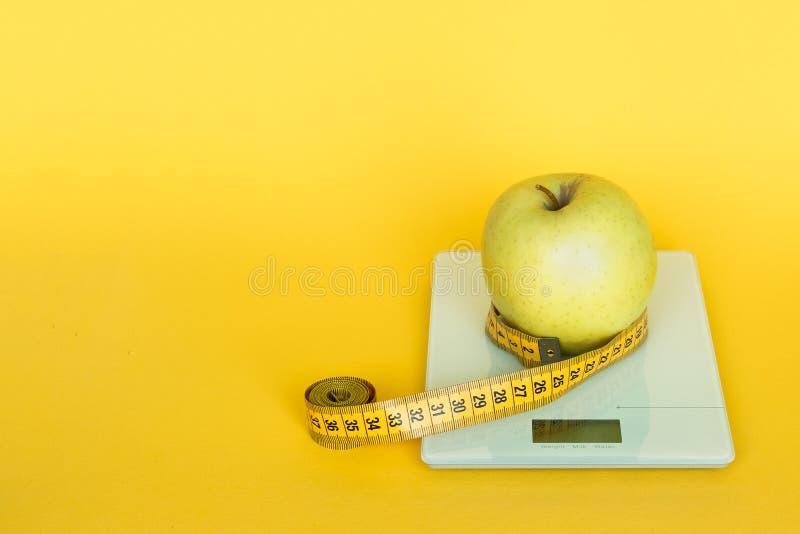 Faça dieta o conceito Maçãs e escalas da cozinha do tampo da mesa e linha de medição da fita no fundo amarelo fotografia de stock royalty free