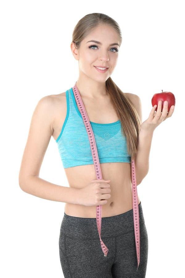 Faça dieta o conceito Mulher bonita nova com maçã e fita de medição no fundo branco imagens de stock royalty free