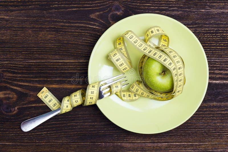 Faça dieta o conceito representado pela maçã verde fresca na placa com o grito imagem de stock royalty free