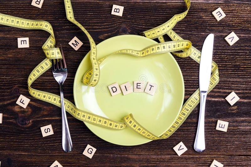 Faça dieta o conceito representado a placa, a cutelaria e pela medição amarela fotos de stock royalty free