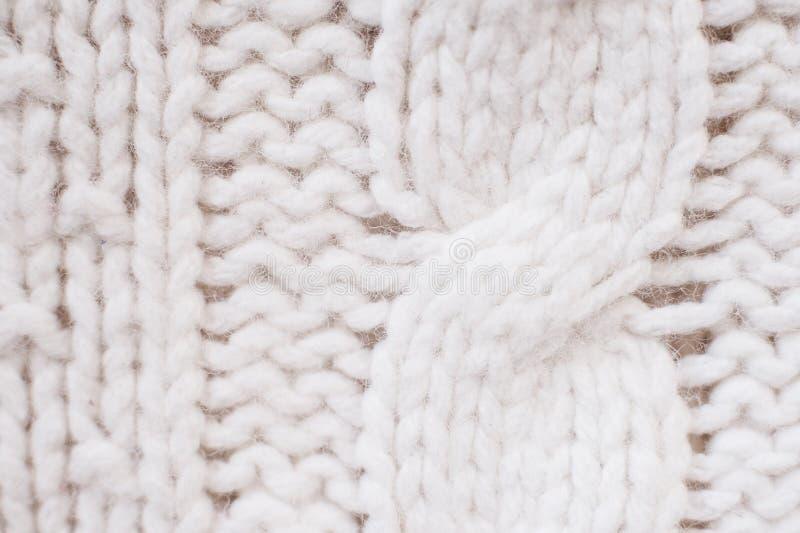 Faça malha a textura as lãs brancas da tela feita malha com teste padrão do cabo como o fundo fotos de stock royalty free