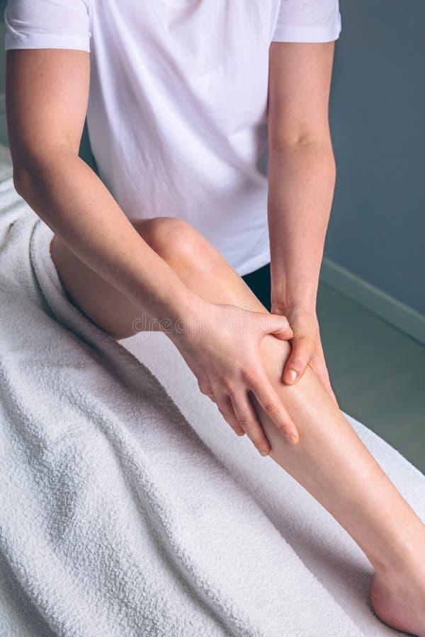 Faça massagens as mãos do terapeuta que fazem o tratamento linfático da drenagem à mulher imagens de stock