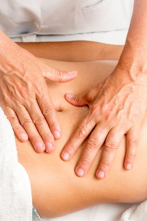 Faça massagens o terapeuta Massaging um estômago do ` s da mulher fotografia de stock
