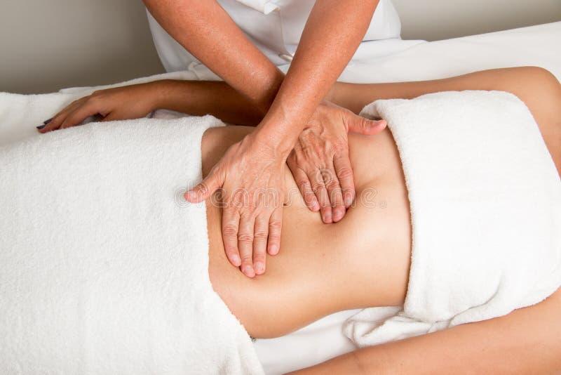 Faça massagens o terapeuta Massaging um estômago do ` s da mulher imagem de stock