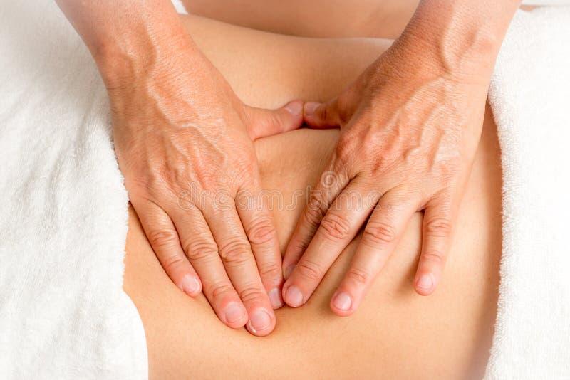 Faça massagens o terapeuta Massaging um estômago do ` s da mulher foto de stock royalty free