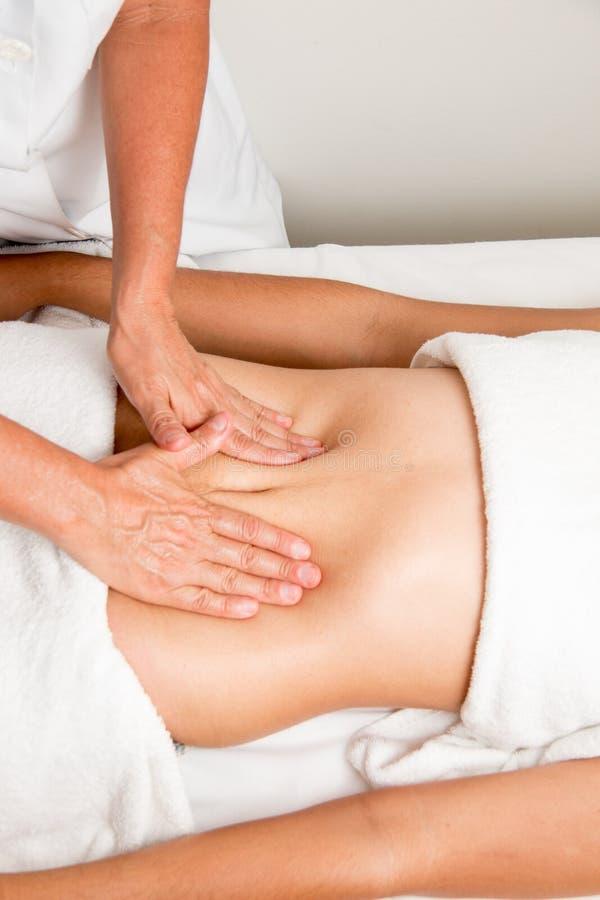 Faça massagens o terapeuta Massaging um estômago do ` s da mulher imagem de stock royalty free