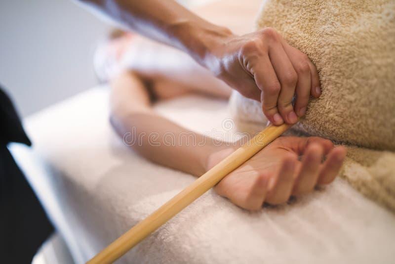 Faça massagens o terapeuta que usa a ferramenta de madeira para fazer massagens o paciente foto de stock