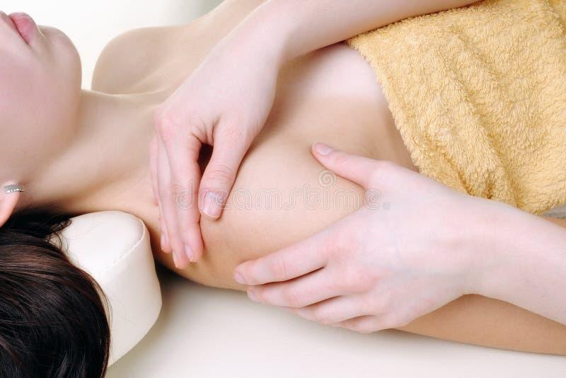 Faça massagens os braços de uma mulher nova fotografia de stock royalty free