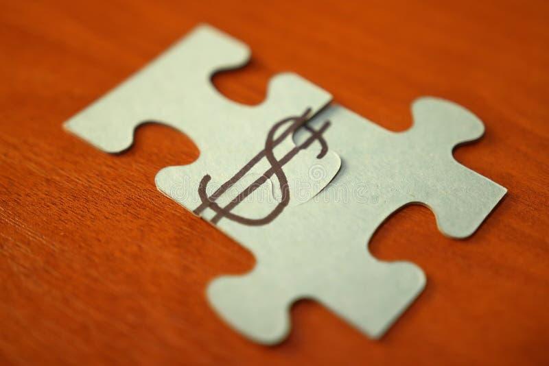Faça o conceito do dinheiro Os enigmas põem no sinal de dólar sinal de dólar em duas porções do enigma na tabela de madeira Dinhe fotos de stock royalty free