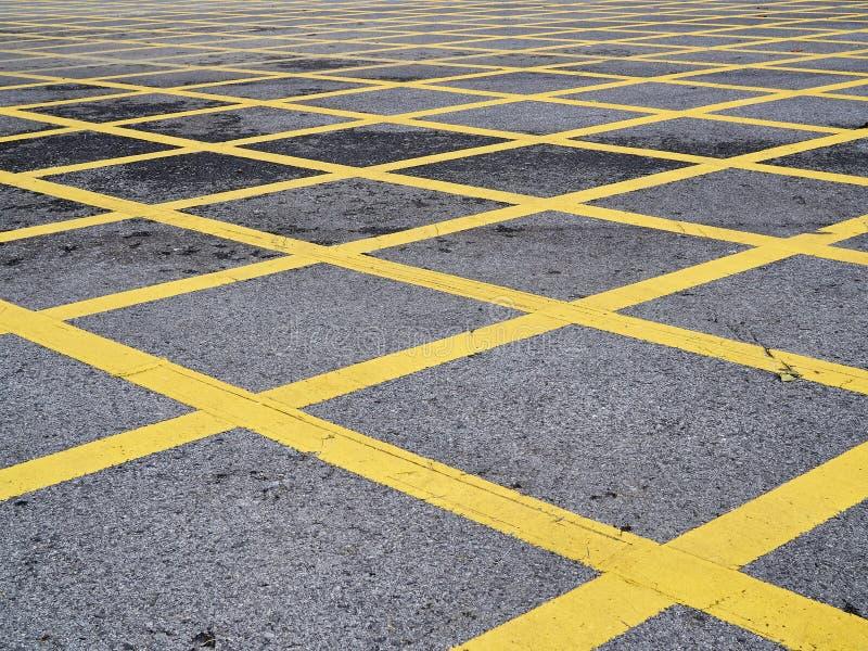 Faça o sinal transversal amarelo de estacionamento no serface da estrada fotografia de stock